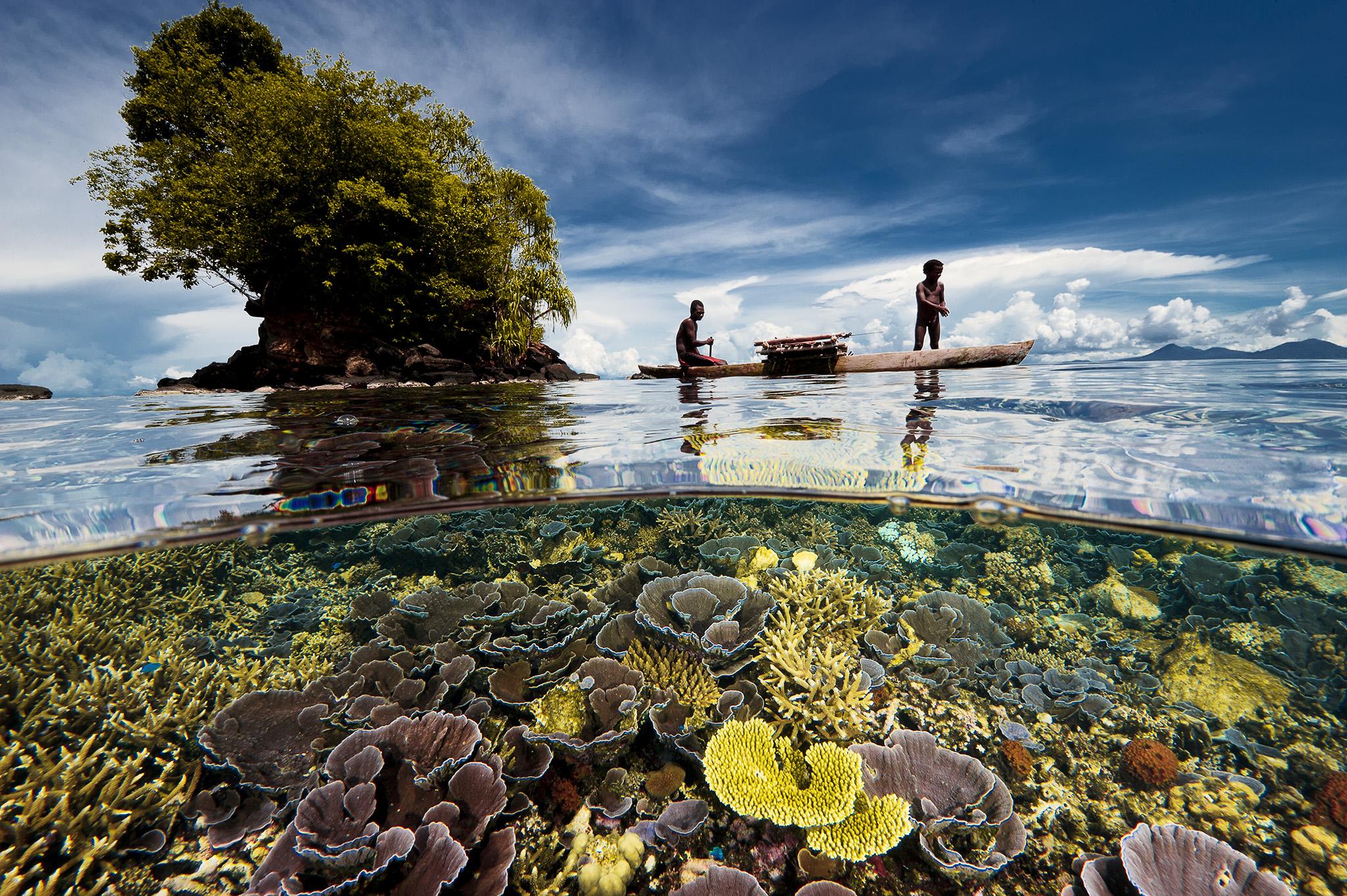 Pêcheurs père et fils. Un jardin coloré de coraux entoure un petit îlot près de la péninsule de Willaumez dans la baie de Kimbe, en Papouasie- Nouvelle-Guinée. Alors que je photographie ce paradis d'eaux peu profondes, un père et son fils, deux pêcheurs, ont glissé devant mon objectif pour compléter cette scène. La Papouasie-Nouvelle-Guinée est une pierre angulaire du Triangle de Corail, une région océanique bordée par la Papouasie-Nouvelle-Guinée, les Philippines et l'Indonésie, connue pour sa biodiversité marine extrême.